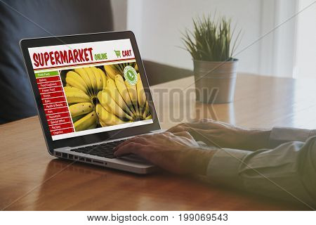 Man doing his grocery shopping by internet with a laptop at the office