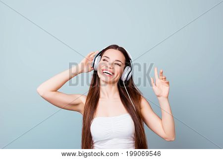 Dreamy Charming Young Lady With Toothy Smile In Modern Headphones. She Is Dreamy And Happy, Listenin