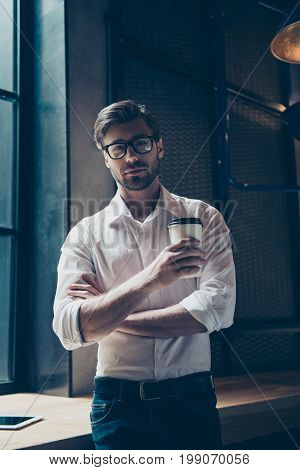 Successful Young Boss With Bristle, In Glasses, Well Dressed Is Having Coffee In A Dark Work Station