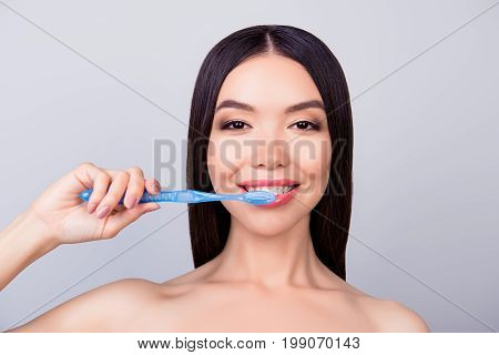 Dental Health Concept. Gorgeous Asian Girl Is Cleaning Her Teeth With Blue Tooth Brush, On Light Gre