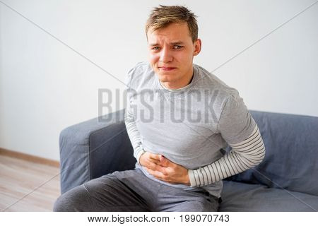 A portrait of a guy suffering from a stomachache