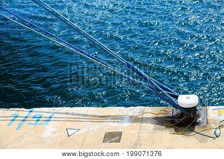 Blue Ropes to Black and White Bollard on Concrete Pier