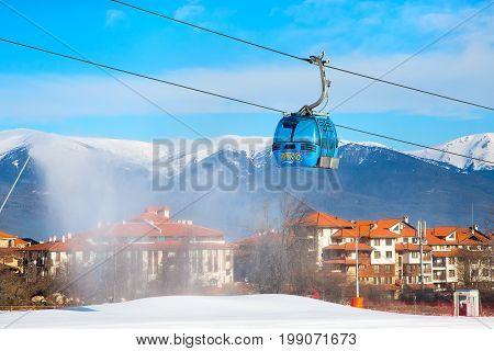 Bansko, Bulgaria - February 19, 2015: Ski resort Bansko, Bulgaria panorama with cable car ski lift cabin, snow mountains and houses in winter