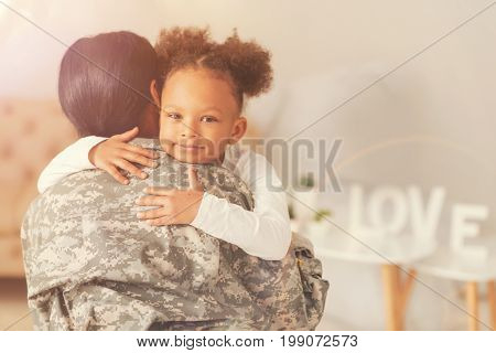 Happy child. Pretty curly girl hugging her mother wearing a military uniform after her long period of absence and serving in the military.