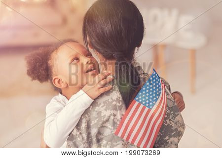 I love you. Cute little girl with an American flag in her hand hugging her mother in a military uniform and whispering something to her ears