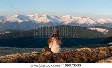 Rearview Shot Of A Female Enjoying Gorgeous View In The Early Morning Sitting On Top Of A Mountain R