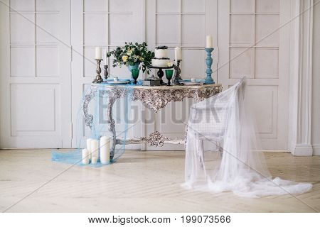 The beautiful wedding decorate table, candles, flowers in white studio