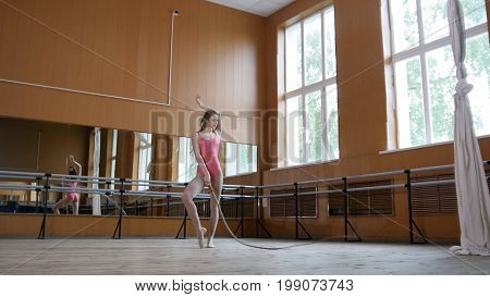Dance with whip - girl gymnast perform circus exercise, telephoto