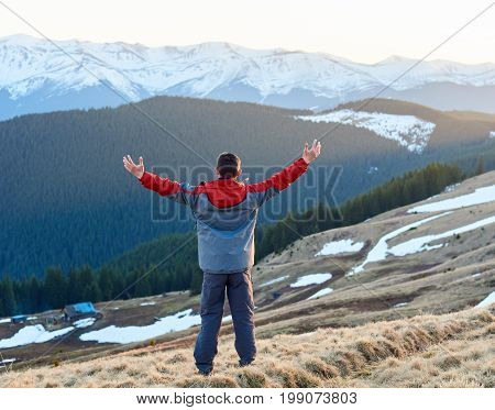 Rear View Of Male Tourist With Raised Hands Enjoying Beautiful Panorama In The Evening On The Blurre
