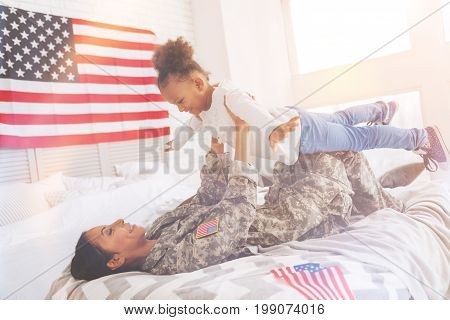 Cute game. Happy young mother in a US military uniform lying on the bed and lifting up her little daughter pretending to be and airplane