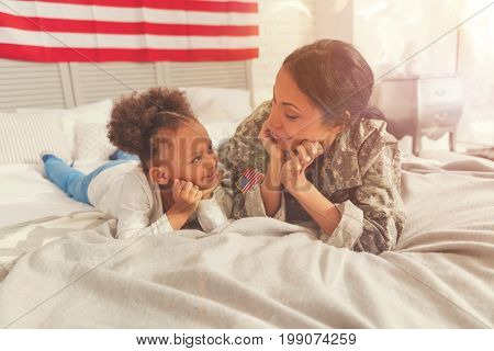 Looking with admiration. Cute little curly girl and her beautiful mother in a US military uniform lying on the bed, resting their chins on the hands and looking at each other admiringly