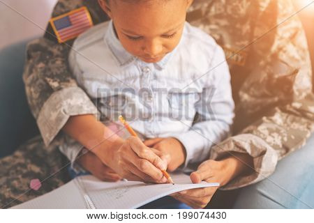 Busy bee. The close up of a female wearing a US military uniform, having a child in the lap and putting down something into the notebook