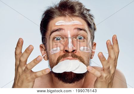 Man with a beard on a white isolated background, wadded disks, cosmetic cream, portrait. emotions.
