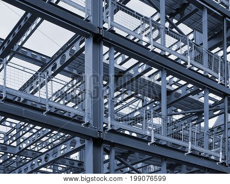 metal framework of new building development with a network of blue steel girders and safety fencing