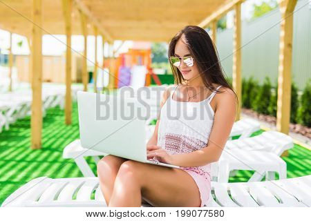 Working Even On Vacation. Attractive Young Woman In Sunglasses And Hat Is Lying On A Chaise-longue N
