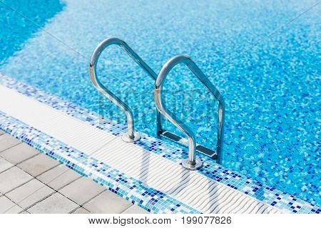 Grab Bars Ladder In The Blue Swimming Pool. Summer.