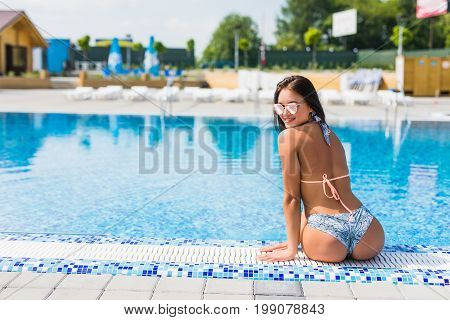 Beautiful Young Woman Sitting On Edge Of Swimming Pool. Summer Vocation.