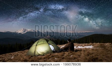 Male Tourist Have A Rest In His Camping In The Mountains At Night. Man Enjoying Night Scene Near Tou