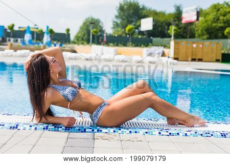 Beautiful Sexy Luxurious Girl Lies On The Edge Of The Swimming Pool, Sunbathing, Tanned Perfect Body