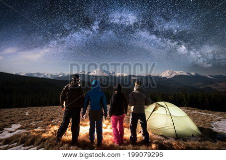 Silhouette Of Four People Standing Together Beside Camp And Tent Under Beautiful Night Sky Full Of S