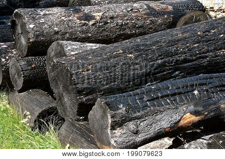 Charred wooden logs after a fire are left blackened