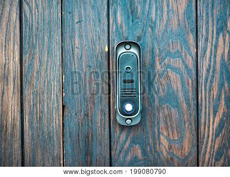 intercom near a grunge old wooden door