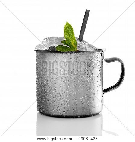 Drink with leaves of mint in the metal mug isolated on white background