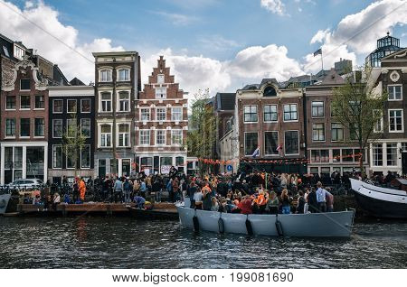 Amsterdam Netherlands - 27 April 2017: Local people and tourists dressed in orange clothes ride on boats and participate in celebrating King's Day along the canal of Amsterdam. Typical architecture