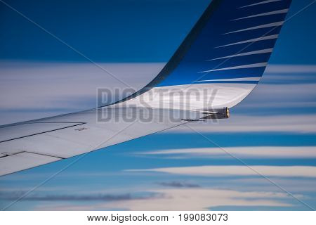 The tip of the wing of the plane against the blue sky. The wing of the plane against the sky and clouds. View of the wing tip of the aircraft. Wing of an airplane against a background in the sky. A view of the wing of an airplane on the background of the