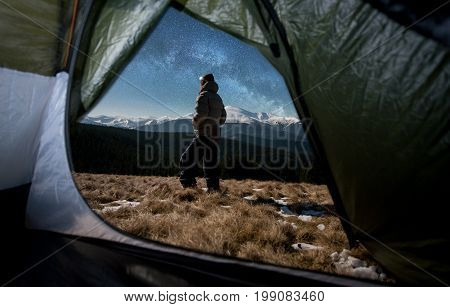 View From Inside A Tent On The Male Tourist In His Camping In The Mountains At Night. Man With A Hea