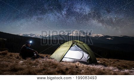 Man Hiker Enjoying Night Scene In His Camping In The Mountains At Night. Man With A Headlamp Sitting