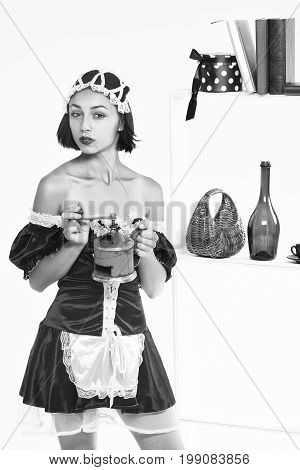girl with pretty face in sexy servant costume and lace cap holding handle coffee grinder posing at kitchenware on shelves isolated black and white
