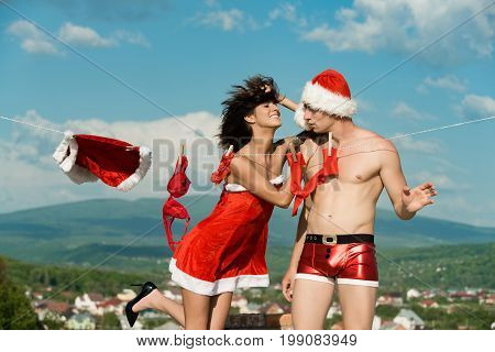 Christmas man and woman family. Couple of happy man and girl hanging clothes for drying. Xmas red costume on rope with pin. Laundry and dry cleaning. New year guy with muscular body on blue sky.
