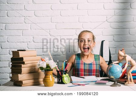 Schoolgirl With Happy Face Sits At Her Desk