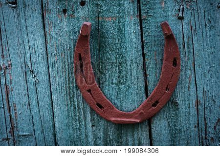 Old horseshoe in vintage blue wooden background