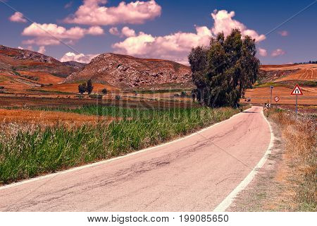 Winding Asphalt Road between Spring Fields of Sicily at Sunset