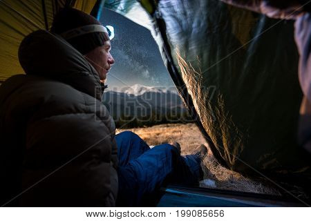 View From Inside A Tent On The Male Tourist Enjoying In His Camping At Night. Man With A Headlamp Si