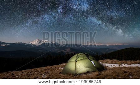 Night Camping. Illuminated Tourist Tent Under Beautiful Night Sky Full Of Stars And Milky Way. On Th