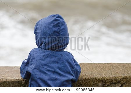 Boy In Blue Jacket With Hood Stands With His Back Against The Pier Against The Background Of Sea Wav