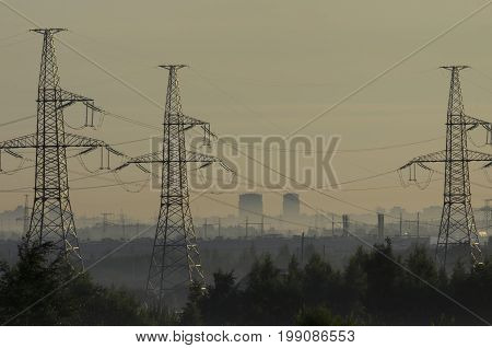 Towers of power lines in the pre-dawn fog on the outskirts of the city