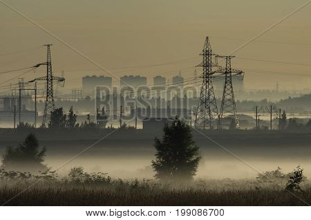 Fog over fields and towers of power lines on the outskirts of the city on the background of power lines