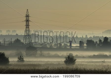 Fog over fields and tower of power lines on the outskirts of the city on the background of power lines