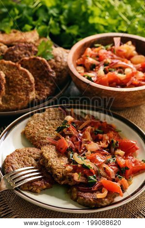 Eggplant fritters served with stewed tomatoes and onion, vegetarian food.