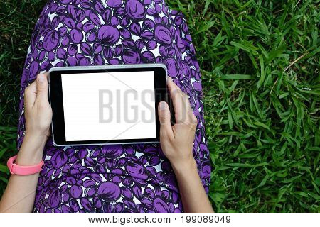 Anonymous woman in purple dress relaxing on green grass with tablet. Rear view. Crop shot with horizontal orientation screen template.