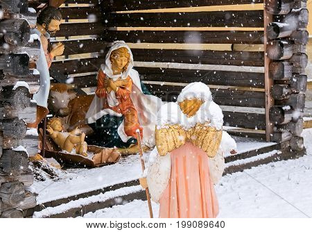 Christmas nativity scene with statues at full size under a snowfall in December in a mountain town, italy