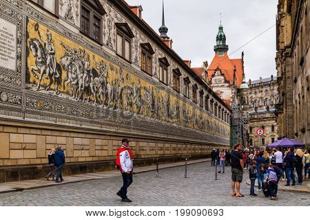 Dresden Germany - July 26 2017: Tourists walk near the famous wall tile mural from Meissen porcelain Procession of princes in the historical part of beautiful Dresden.