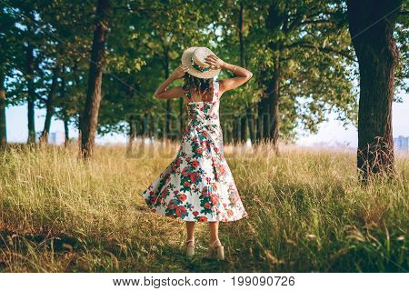 Charming Brunette Girl With A Curly Hair In A Straw Hat Looks Ahead. Traveling. Outdoors