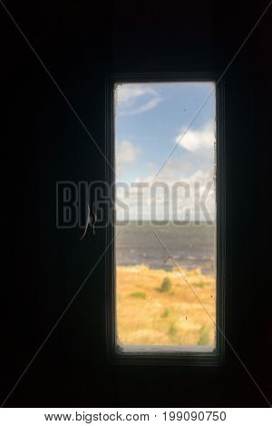 A glimpse of the Baltic Sea with sand dunes through a window on a lighthouse