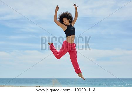 Young Pretty Sportswoman Jumping On Beach Raising Hands
