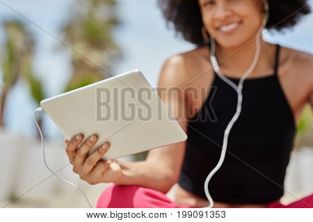Happy Afro American Woman Holding Tablet With Plugged Earphones